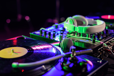 close up view of sound mixer with vinyl, microphone and headphones in nightclub