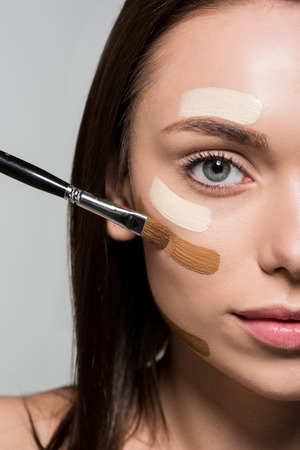 young attractive woman applying tonal foundation on face isolated on grey