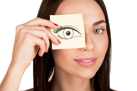 young woman covering eye with cartoon style drawn eye on sticker isolated on white