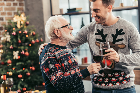 senior man and his son celebrating christmas together and toasting with wine