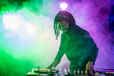 professional african american DJ in headphones with sound mixer in nightclub