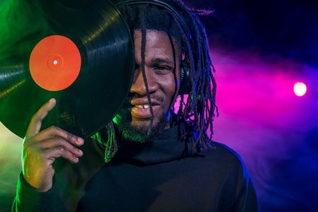 portrait of professional african american club DJ in with vinyl