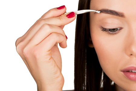 young woman doing eyebrow correction isolated on white