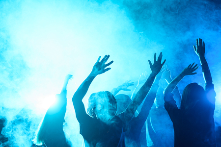people dancing on party in nightclub with blue back light