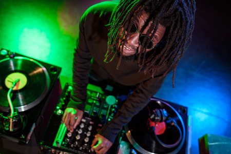 professional african american DJ with sound mixer in nightclub  Stock Photo