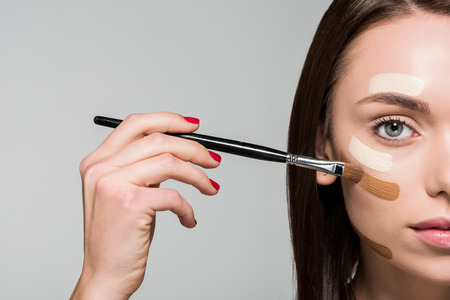 young beautiful woman applying tonal foundation on face isolated on grey