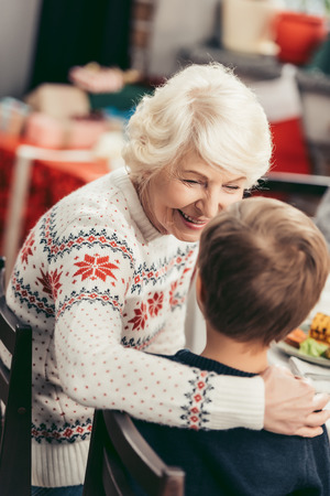 beautiful happy grandmother and little grandson talking at christmas table Standard-Bild
