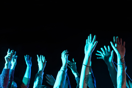 cropped view of hands on music concert in nightclub with blue back light