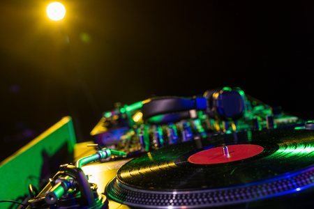 sound mixer and vinyl in nightclub with back light