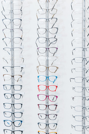blonde female ophthalmologist standing in optics with glasses on shelves Stock Photo