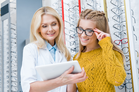 optician with digital tablet helping client to choose eyeglasses in optics Stockfoto