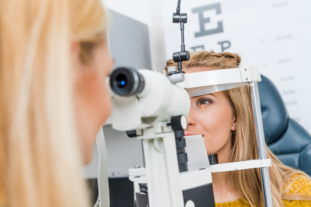 optometrist examining patient through slit lamp in clinic