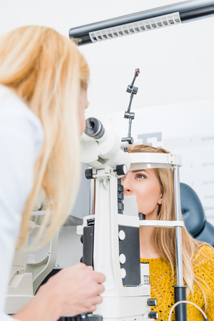 optician examining patient through slit lamp in clinic