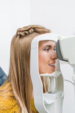 smiling patient examining her eyes with slit lamp in clinic