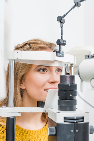 beautiful patient examining her eyes with slit lamp in clinic Stok Fotoğraf