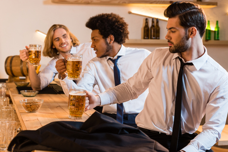 young multiethnic businessmen drinking beer and talking in bar Banco de Imagens