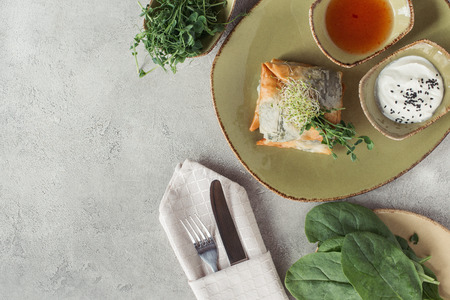 food composition with samosas in phyllo dough stuffed with spinach and paneer decorated with germinated seeds of alfalfa and sunflower served on plate on grey tabletop Stock Photo