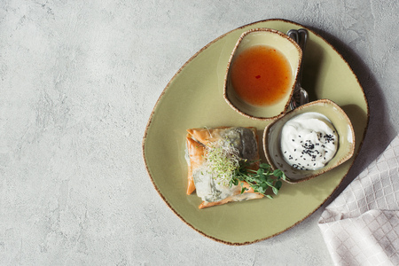 flat lay with samosas in phyllo dough stuffed with spinach and paneer decorated with germinated seeds of alfalfa and sunflower served on plate on grey surface Banco de Imagens