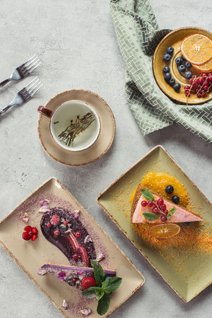 flat lay with sweet carrot cake with berry filling, blueberry cake served with mint leaves and violet petals, cup of herbal tea and cutlery on grey tabletop