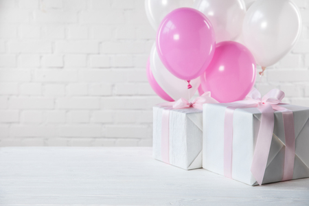 Presents on table with white and pink balloons on white brick wall background