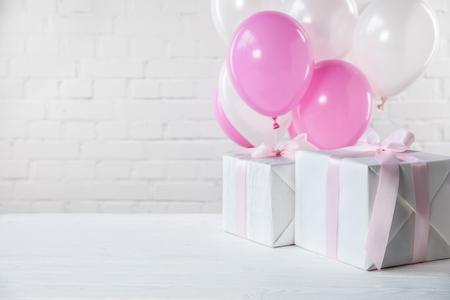 Geschenke auf dem Tisch mit weißen und rosa Luftballons auf weißem Backsteinmauerhintergrund