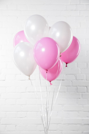 Bunch of pink and white balloons on white brick wall background
