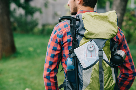 cropped shot of young man traveler with backpack, compass and map