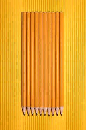 top view of arranged graphite pencils placed in row on yellow Reklamní fotografie