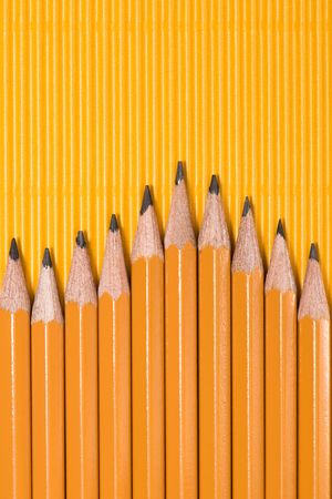top view of graphite pencils placed in row on yellow Stock Photo - 104569870