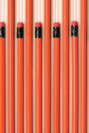 top view of red graphite pencils with erasers placed in row on beige Reklamní fotografie