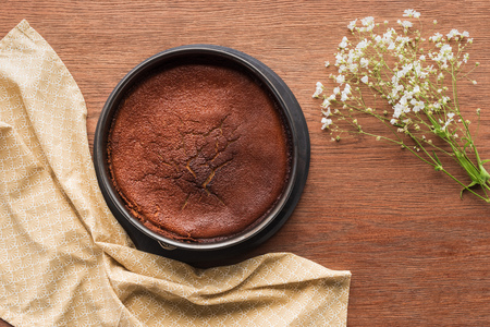 top view of delicious homemade brownie and beautiful white flowers on wooden table