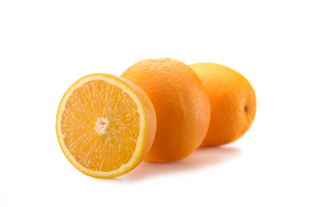 close up view of wholesome oranges with cut piece isolated on white Stock Photo
