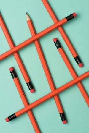 elevated view of arranged red graphite pencils with erasers on green