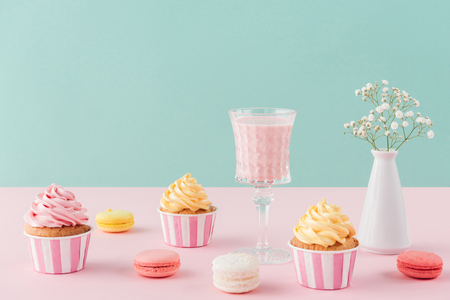 cupcakes and sweet macarons and glass of milkshake on pastel background