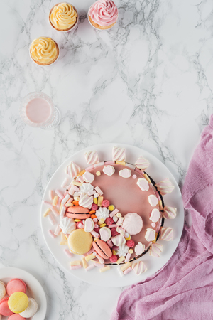 flat lay with pink birthday cake with marshmallows, cupcakes and milkshake on marble table