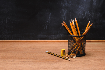 close up view of desk organizer with pencils and sharpener on wooden table in front of empty chalk board in school