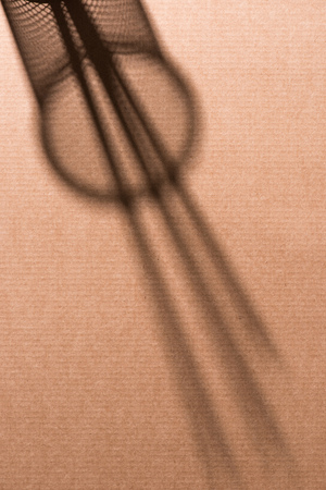 top view of shadow of desk organizer with pencils on cardboard