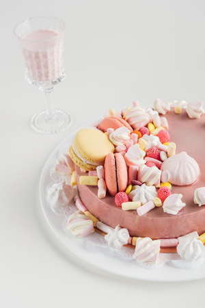 pink cake with marshmallows and macarons on plate and milkshake in glass