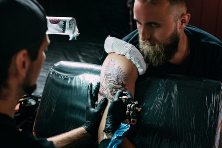 selective focus of tattoo artist in gloves with tattoo machine working on tattoo on shoulder in salon