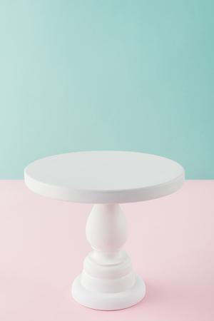 empty white cake stand on pink and turquoise background with copy space Stock Photo