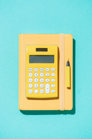 top view of arrangement of calculator, pencil and notebook on blue backdrop Stock Photo