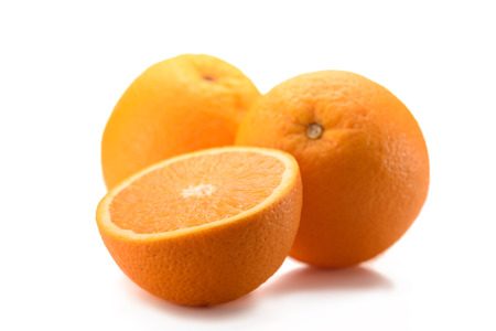 close up view of wholesome oranges with cut piece isolated on white Imagens
