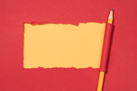 top view of ripped red paper and wrapped pencil on yellow