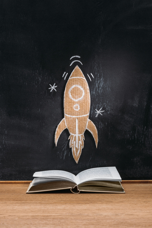 close up view of cardboard rocket on blackboard and opened book on wooden surface