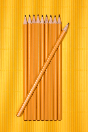 elevated view of graphite pencils placed in row on yellow
