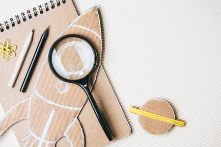 Draufsicht der handgemachten Papprakete und des Planeten, der Lupe, des Notizbuchs und der Stifte auf weißem Hintergrund Standard-Bild