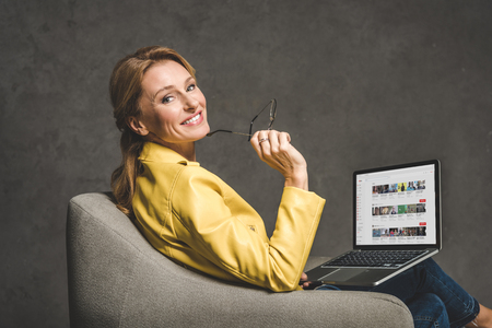 smiling mature woman using laptop with youtube website and sitting in armchair