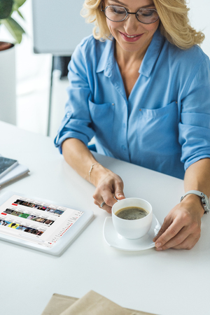 smiling blonde businesswoman with cup of coffee using tablet with youtube website