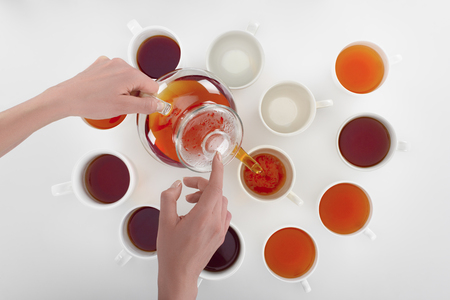 partial view of person pouring herbal tea in cups on grey Stock Photo