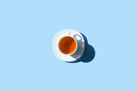 top view of cup of healthy herbal tea isolated on blue